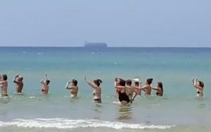 YOUTUBE Pozzallo, balli di gruppo in mare. Sullo sfondo la nave Maersk carica di migranti