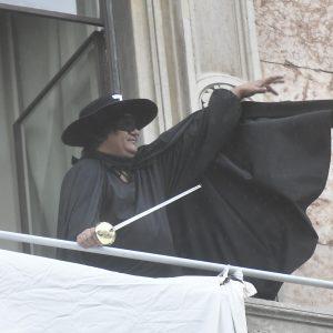 """Il manifestante vestito da Zorro srotola uno striscione da un balcone in piazza DUomo: """"Restiamo umani"""""""