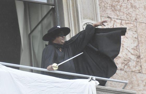"""Il manifestante vestito da Zorro srotola uno striscione: """"Restiamo umani"""""""