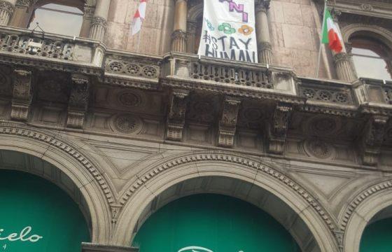 """Lo striscione srotolato da un balcone di palazzo Galleria: """"Restiamo umani"""""""