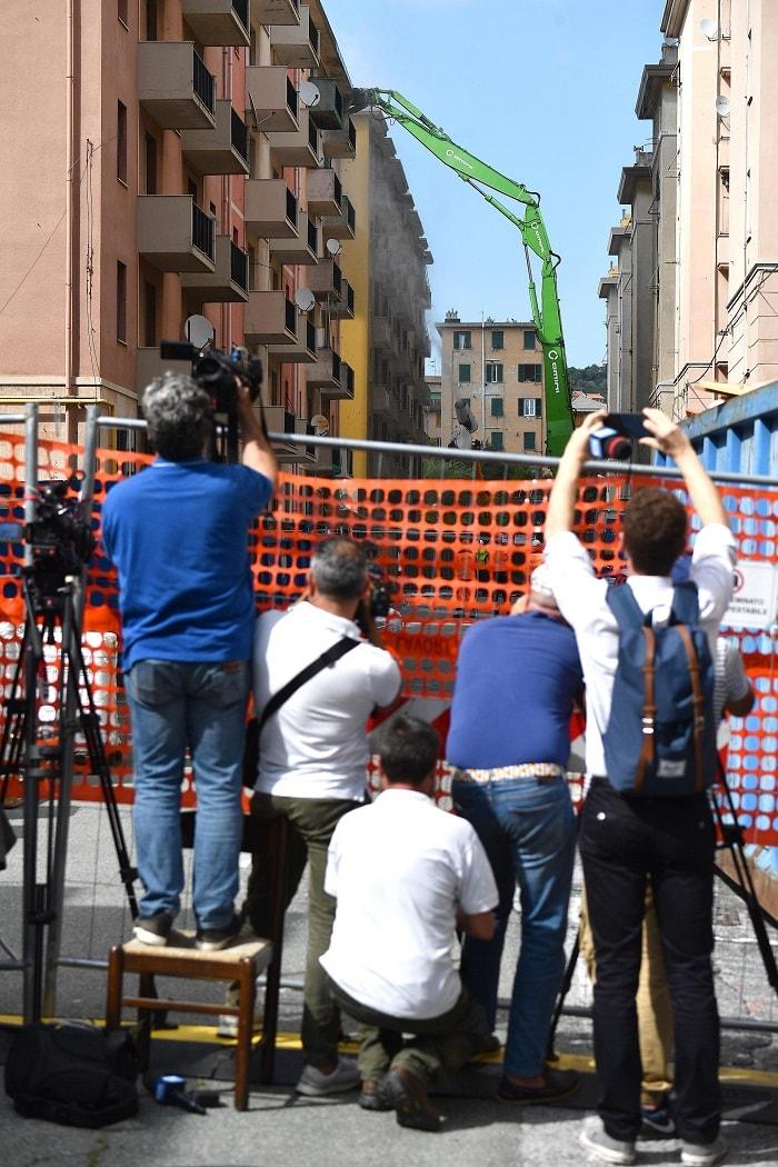 giornalisti e curiosi osservano demolizione ponte morandi
