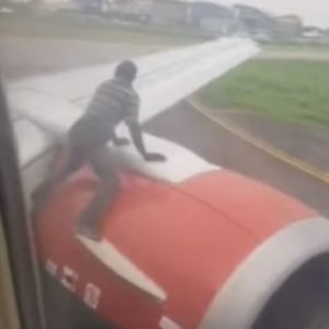 nigeria, uomo sale su ala aereo