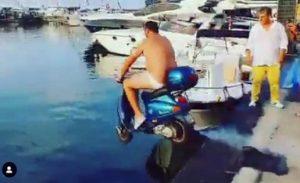 Catello, in costume, tenta il tuffo in mare con lo scooter dopo la scommessa con Mario Balotelli.