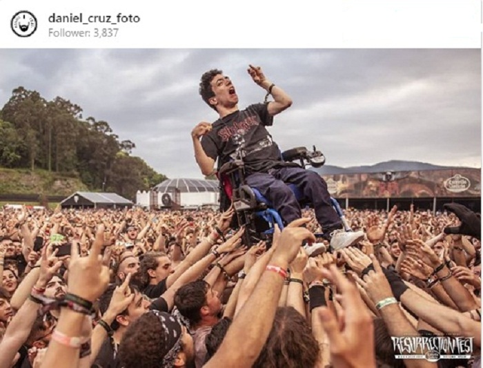 Disabile in carrozzina sollevato in aria dal pubblico al concerto. La foto che commuove