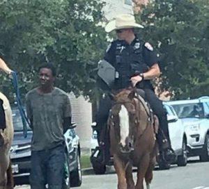 Poliziotti a cavallo trascinano un uomo nero al guinzaglio: Stati Uniti, Texas, 2019
