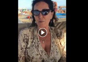 Daniela Santanché parla in spiaggia. Ma dietro di lei un uomo si lava tutto...VIDEO