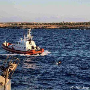 La motovedetta della Guardia Costiera recupera il migrante in mare