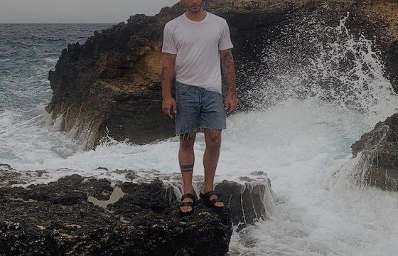 Stefano De Martino spaventa i fan: la foto in ciabatte sullo scoglio col mare agitato