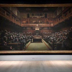 """Banksy, asta record per il dipinto """"Parlamento devoluto"""": venduto a 11,1 milioni di sterline"""