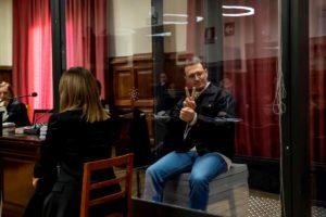Igor il russo fa il segno di vittoria dalla gabbia di vetro durante il processo in Spagna