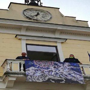 Cesa (Caserta), Dio smaterializza il Covid-19: la raffigurazione sulla facciata del comune