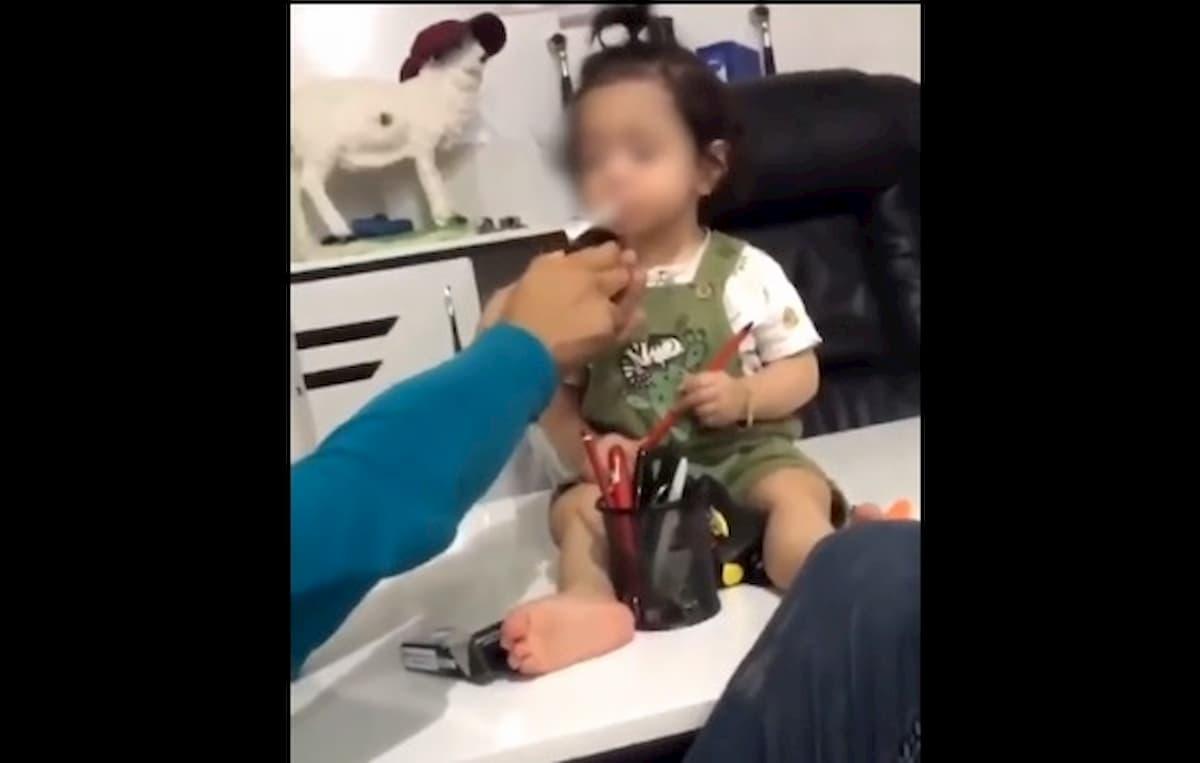 Bimba di 3 anni fuma una sigaretta e lo zio ride