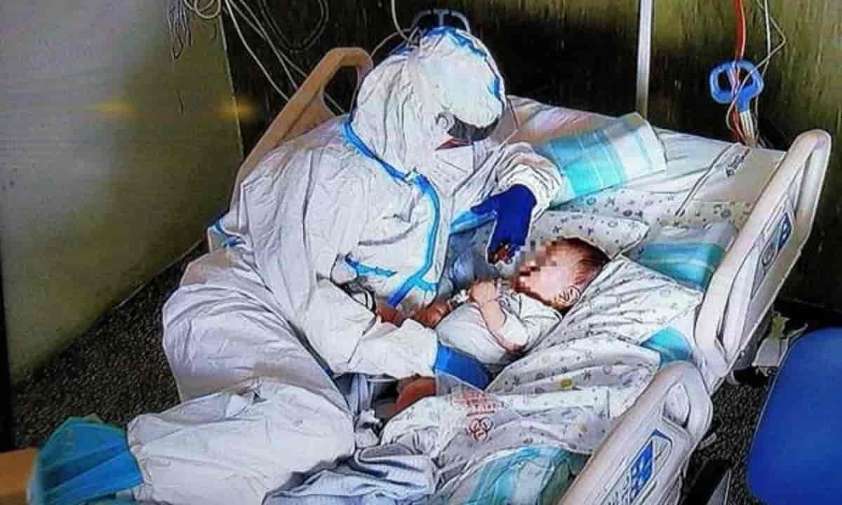 La carezza dell'infermiera al bimbo di 7 mesi malato di Covid, FOTO simbolo all'ospedale di Ancona
